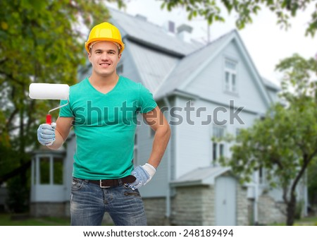 repair, construction, people, building and maintenance concept - smiling male manual worker in protective helmet holding paiting roller over house background - stock photo
