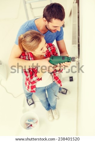 repair, interior design, building, renovation and home concept - smiling couple drilling hole in wall at home - stock photo