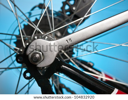 repair of a bicycle with a metal wrench - stock photo