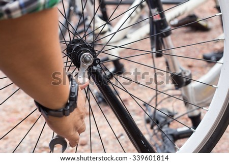 repair of a bicycle with a wrench. - stock photo