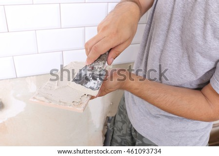 Repair of apartments. Tiler hands in the process of laying white rectangular tiles on the kitchen wall or bathroom wall Rectangular white ceramic tile with a chamfer on the kitchen wall.