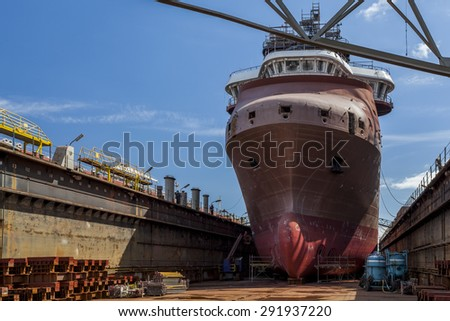 Repair of the ship on a dry dock at the shipyard - stock photo