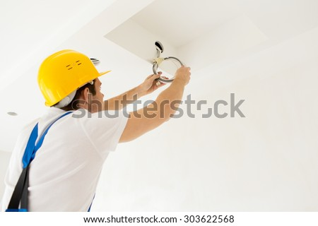 repair, renovation, electricity and people concept - close up of builder or electrician running wires indoors - stock photo