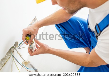 repair, renovation, electricity and people concept - close up of electrician hands with screwdriver fixing socket - stock photo