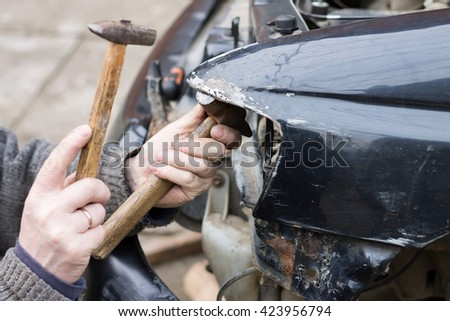 Repair service worker fix damaged car after crash on the road. Working with hammer to align metal body. - stock photo