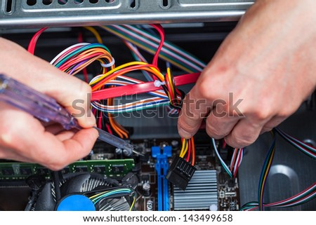 Repairing broken computer with a screwdriver - stock photo