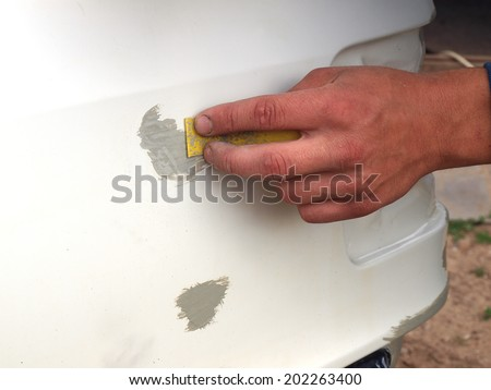 Repairing car body by puttying close up - stock photo
