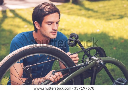 Repairing his bike. Confident young man fixing his bike while kneeling on grass - stock photo
