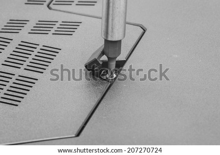 Repairing laptop: screw driver and bolt, close image. - stock photo