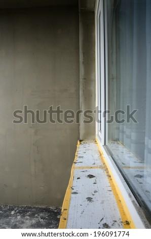 Repairing of balcony, gray plaster and dirty white window. - stock photo