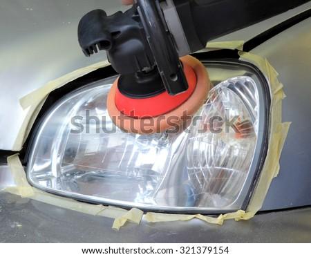 Repairing of  modern car headlight, closeup of light and tool - stock photo