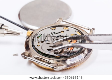 Repairing of watch - replacing battery in quartz watch close up - stock photo