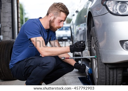 Repairman changing car wheel with cross wrench.