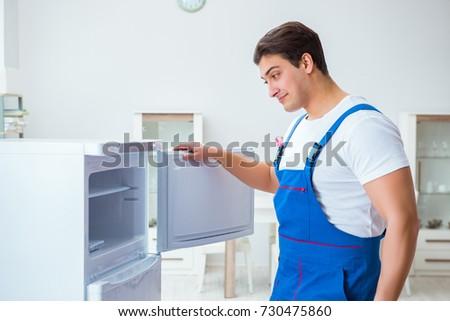 Repairman contractor repairing fridge in DIY concept