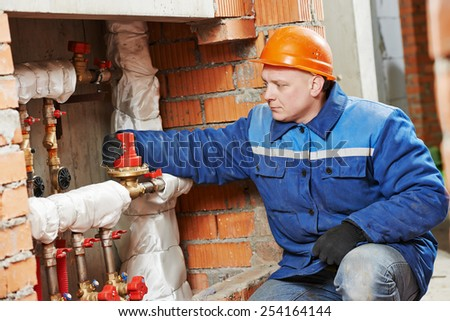 repairman engineer of engineering system or heating system installer open the valve equipment in a boiler house - stock photo