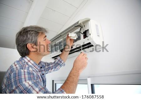 Repairman fixing air conditioner unit - stock photo
