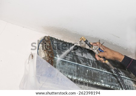 Repairman fixing and cleaning air conditioner unit - stock photo