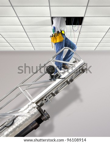 Repairman fixing cables in the ceiling standing on a telescopic ladder - stock photo