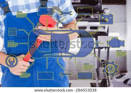 Repairman holding adjustable pliers against auto repair shop - stock photo