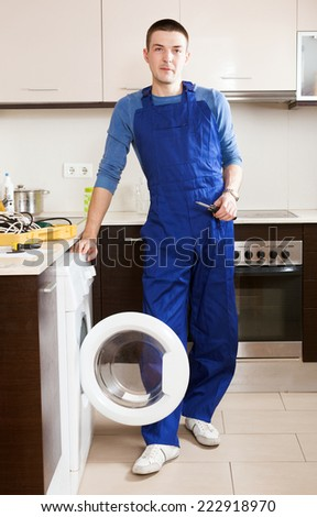 Repairman in uniform repairing washing machine at kitchen - stock photo