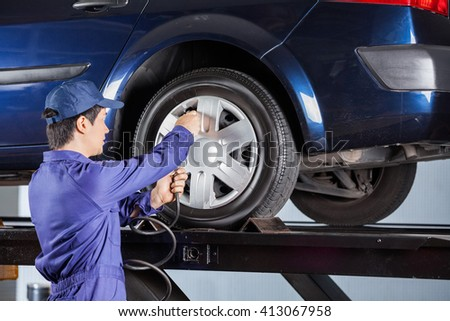 Repairman Inflating Tire Of Lifted Car - stock photo