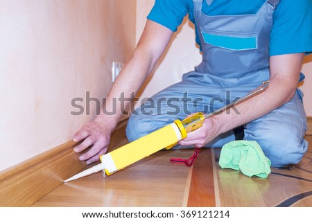 Repairman Installing Skirting Board Oak Wooden Floor with Caulking Gun Silicone from Cartridge. Flooring with Wooden Batten Repair. - stock photo