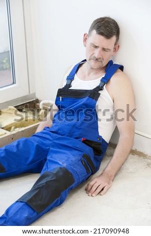 repairman lying on the floor and sleeping - stock photo