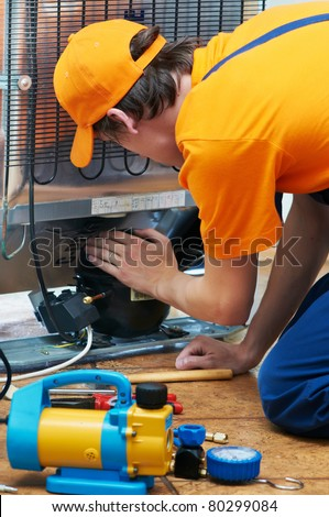 Repairman makes refrigerator appliance troubleshooting and maintenance works - stock photo