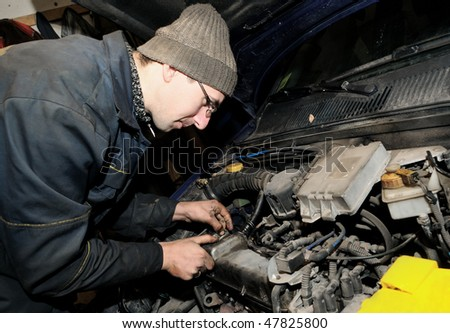 repairman mechanic at car repairing work using a tool