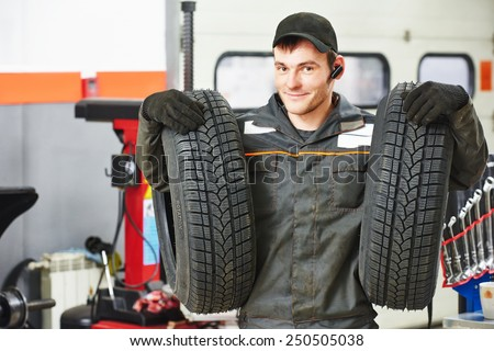 repairman mechanic portrait in car auto repair or maintenance shop service station with automobile wheel tire - stock photo