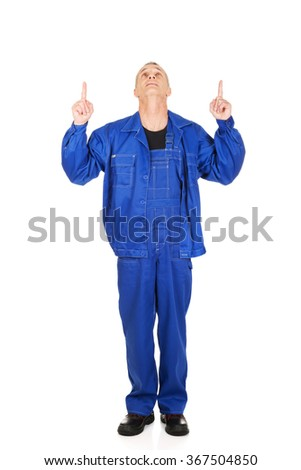 Repairman pointing up with both hands - stock photo