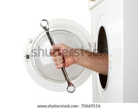 Repairman servicing washing machine. Isolated on white - stock photo