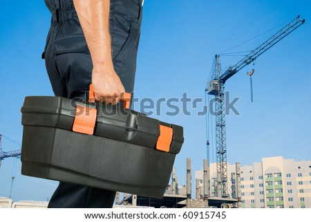 repairman with box of instruments on building background - stock photo