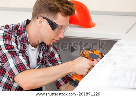 repairman with electric drill in new apartment - stock photo