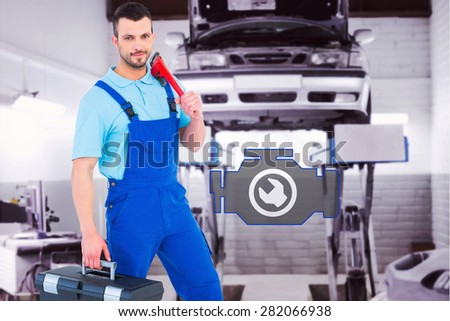 Repairman with toolbox and monkey wrench against auto repair shop - stock photo