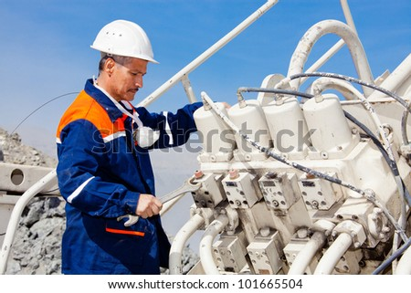 repairman worker repairing a hydraulic excavator system - stock photo