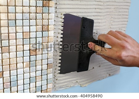 Repairs in the apartment: installing mosaic tile on wall. / A worker covers the wall with adhesive using a notched trowel. - stock photo