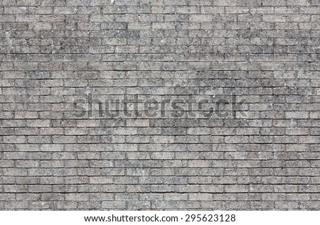 Repeating gray brick wall texture typically found in developed areas. The image is a loop ready seamless texture file, allowing the picture to be tiled and used as an infinite scrolling background. - stock photo