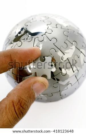 Replacing last piece of jigsaw globe - stock photo