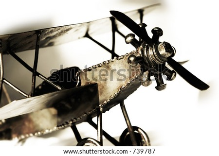 Replica of vintage biplane, close up with shadow on white - transportation and travel.
