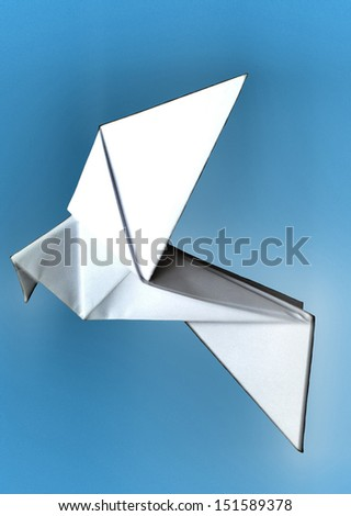 representation of a glowing white origami paper dove on a blue background, referring to concepts such as peace, freedom, lightness, the art of flying, as well as environmental concerns