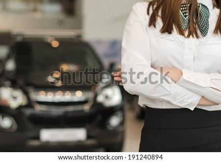 Representative female in car dealership salon. - stock photo