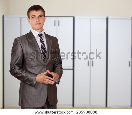 Representative young male businessman in the office.  One person, dressed according to business dress code, located inside the office interior - stock photo