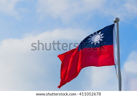 Republic of China (ROC) on Taiwan flag against blue sky and clouds - stock photo
