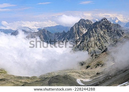 Republic of North Ossetia-Alania, Russia. View from cirque of Century Pass and Three Dwarfs Pass to Kursk K-141 Mount, Dashikhokh Mount, Dashivtsek Pass and clouds over ravine of Bilyagidon river. - stock photo