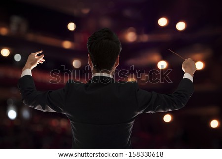 rera view of young conductor with baton raised at performance - stock photo