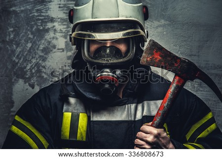 Rescue firefighter man in oxygen mask holds red axe.