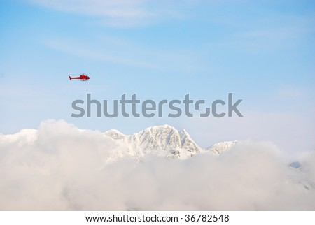 Rescue helicopter above snow peaks