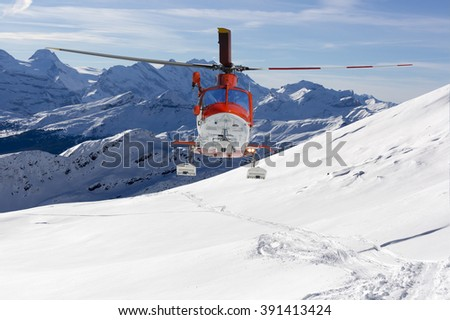 Rescue helicopter lands in snow capped mountains - stock photo