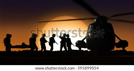 Rescue helicopter with soldiers on ground during sunset - stock photo